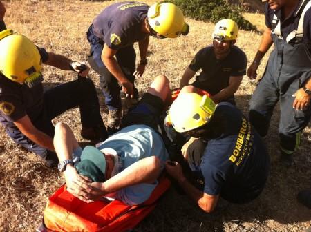 Los bomberos del grupo de rescate en montaña atienden al parapentista herido.
