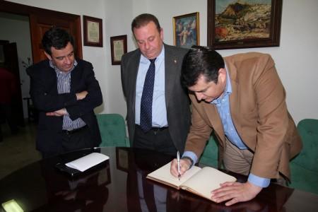 Antonio Sanz firma en el libro de honor del Ayuntamiento de Arcos, ante Núñez y Loaiza.