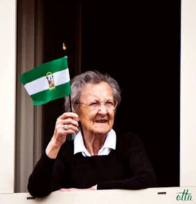Una mujer, con la bandera andaluza.