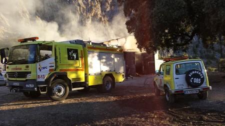 Vehículos de bomberos ante el pajar incendiado.