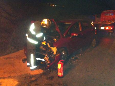 Un bombero, ante uno de los vehículos siniestrados.