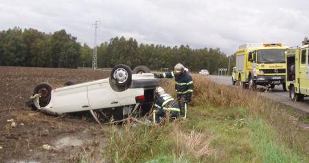Los bomberos, durante su intervención ante el coche accidentado.
