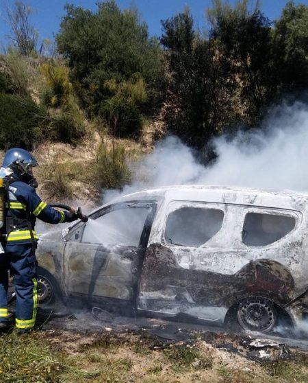 Un bombero sofoca el incendio del vehículo.