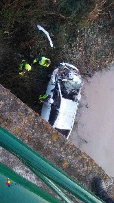 Vehículo accidentado y bomberos en la operación de rescate del cadáver.