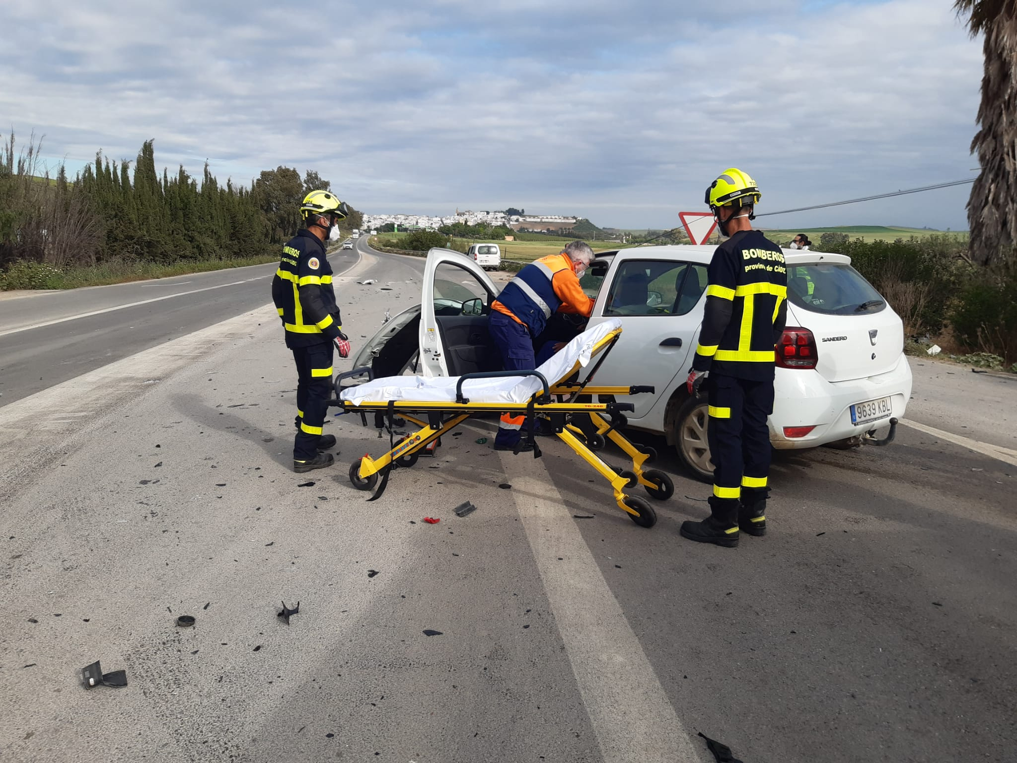 Un sanitario atiende a uno de los conductores en presencia de dos bomberos.